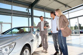 Car seller with couple in car dealership — Stock Photo