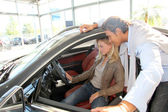 Couple looking inside new car — Stock Photo