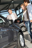 Car seller with couple in showroom — Stock Photo