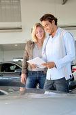 Couple reading car documentation in showroom — Stock Photo