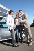 Car seller with couple looking at electronic tablet — Stock Photo