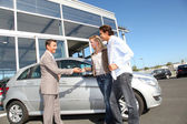 Car seller with couple outside car dealership — Stock Photo