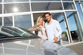 Couple holding car key in automobile dealership — Stock Photo