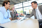 Car seller giving car key to buyers — Stock Photo