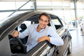 Smiling man sitting at the steering-wheel of brand new car — Stock Photo
