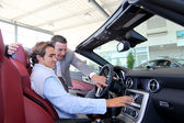 Car seller showing interior details to purchaser — Stock Photo