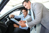 Car seller with car buyer looking at electronic tablet — Stok fotoğraf