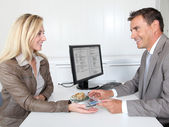 Woman selling gold to banker — Stock Photo