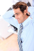 Smiling relaxed businessman in office — Stock Photo