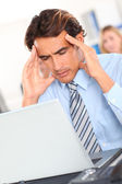 Businessman having a headache in front of laptop — Stock Photo
