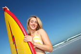 Beautiful blond woman standing with surfboard — Stock Photo