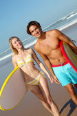 Couple at the beach with surfboard — Stock Photo