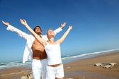 做瑜伽练习在海滩上的情侣 — 图库照片
