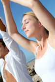 Couple doing yoga exercises on the beach — Stock Photo