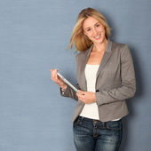 Young woman standing on grey background with touchpad — Stock Photo