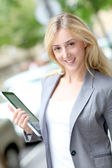 Businesswoman holding electronic tablet in town — Stok fotoğraf