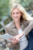 Beautiful woman using electronic tablet in public park — Stock Photo