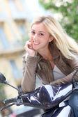 Smiling blond woman sitting on motorbike — Stock Photo