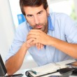 Stock Photo: Portrait of office worker sitting at his desk