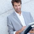 Stock Photo: Handsome mleaning on wall with electronic tablet