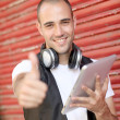 Smiling man using electronic tablet in the street — Stock Photo