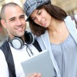 Young couple using electronic tablet in town — Stock Photo