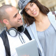 Stock Photo: Young couple using electronic tablet in town