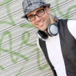 Trendy guy leaning on metal curtain in town — Stock Photo