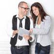 Trendy couple leaning on wall with electronic tablet — Stock Photo