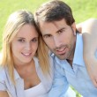 Happy young couple sitting in yard — Stock Photo #18297987