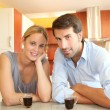 Happy young couple standing in home kitchen — Stok fotoğraf