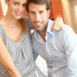 Happy young couple standing in home kitchen - Stock Photo