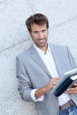 Handsome man leaning on wall with electronic tablet — Stock Photo