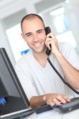 Smiling man answering the phone — Stock Photo