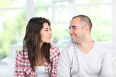 Young couple at home sitting in couch — Stock Photo