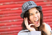 Portrait of trendy girl shouting on the phone — Stock Photo