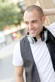 Smiling man listening to music in the street — Stock Photo
