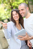 Young couple in public park with electronic tablet — Stock Photo