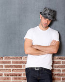 Trendy guy with arms crossed on urban background — Stock Photo