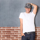 Trendy guy leaning on brick wall — Stock Photo