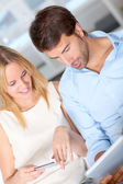 Young couple at home doing online shopping — Stock Photo