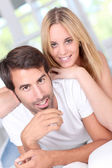 Young couple laying down sofa — Stock Photo