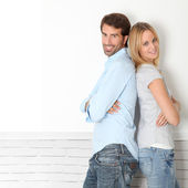 Young couple standing on white wall — Stockfoto