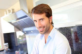 Smiling man standing in domestic kitchen — Stock Photo