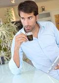 человек, стоящий на кухне с электронные таблетки — Стоковое фото