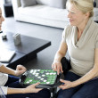 Stock Photo: Young homecarer playing game with elderly woman