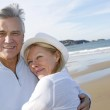 Senior couple walking on the beach in fall season — Stock Photo #26964799