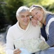 Closeup of happy senior couple sitting by river — Stock Photo