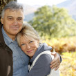 Portrait of smiling senior couple leaning against tree — Stock Photo