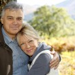 Portrait of smiling senior couple leaning against tree — Stock Photo #26964843
